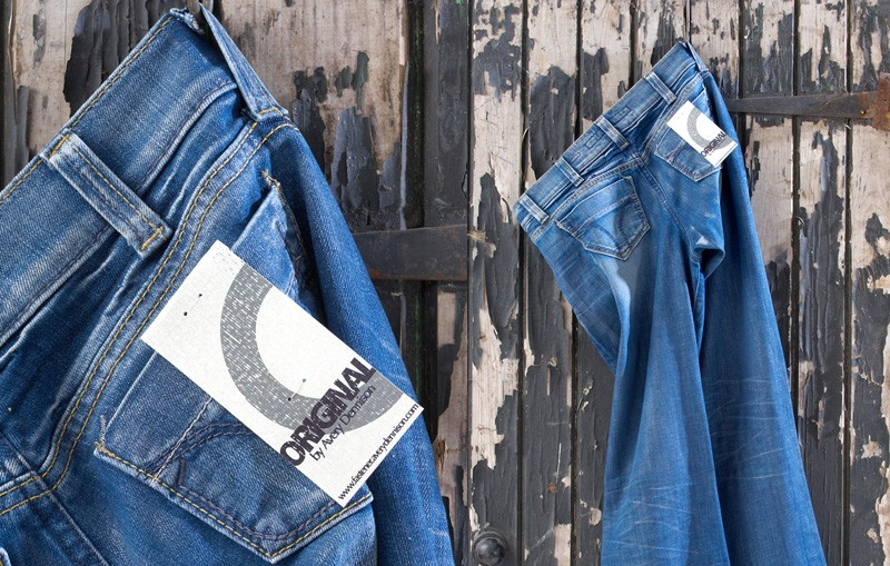 Plastic Staple System tag attached to hanging pair of jeans